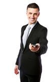 Businessman in a suit giving you a smartphon. Smiling businessman in a suit giving you a smartphone over white background Royalty Free Stock Photography