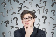Businessman in suit and glasses and 3d question marks. Close up of bespectacled young businessman thinking near a concrte wall with question marks falling Stock Photos