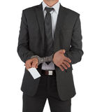 Businessman in suit and handcuffs handing over card Stock Photography