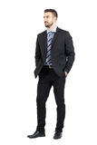 Businessman in suit with hands in pockets smiling and looking away. Full body length portrait isolated over white studio background Royalty Free Stock Image