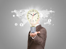 Businessman in a suit hold bulb with clock Stock Images