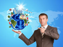 Businessman in a suit hold Earth with buildings Stock Images