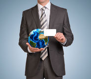Businessman in suit hold empty card and Earth Stock Photography