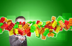 Businessman in suit hold flow of childrens blocks Stock Image