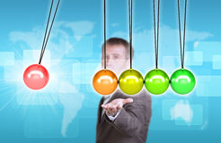 Businessman in suit hold Newtons cradle. World map and rectangles as backdrop Stock Images
