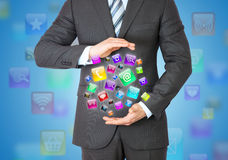 Businessman in a suit holding a app icons. App icons on background Stock Photos