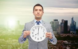 Businessman in suit holding clock with 8 o'clock Stock Photo