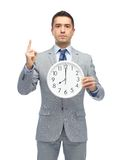 Businessman in suit holding clock with 8 o'clock Royalty Free Stock Images