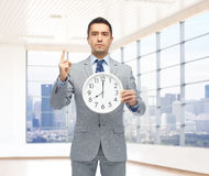 Businessman in suit holding clock with 8 o'clock Stock Image