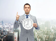 Businessman in suit holding clock with 8 o'clock Royalty Free Stock Photo