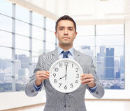 Businessman in suit holding clock with 8 o'clock Stock Images