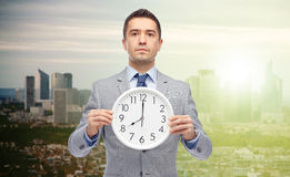 Businessman in suit holding clock with 8 o'clock. Business, people, time management and work concept - businessman in suit holding clock showing 8 o'clock over Royalty Free Stock Photography