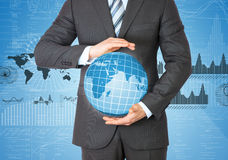 Businessman in a suit holding a globe Stock Image