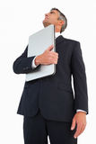 Businessman in suit holding his laptop proudly Stock Image