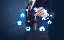 Businessman holding keys with houses around Royalty Free Stock Photos