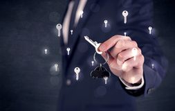 Businessman holding keys with keys around Stock Images
