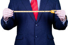 Businessman in suit holding a measuring tape Stock Image