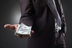 Businessman in suit holding money on dark Stock Photography