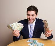 Businessman in suit holding money in his hands dollar and ruble banknote, crazy look Royalty Free Stock Photo