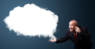 businessman in suit holding a phone and presenting abstract cloud copy space Royalty Free Stock Images
