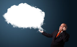 Businessman in suit holding a phone and presenting abstract cloud copy space Stock Photos