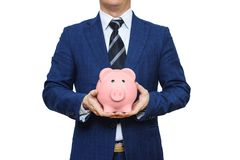 Businessman in suit is holding piggy bank. Businessman holding pig money box. Finance Savings concept.  stock photos