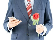 Businessman in suit holding smartphone and red rose Stock Image