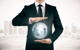 Businessman in suit holding sphere with city Stock Photography
