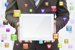 Businessman in a suit holding a tablet computer. Around tablet application icons stock photo