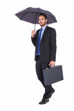 Businessman in suit holding umbrella and briefcase Royalty Free Stock Images