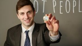 A businessman in a suit holds in his hand a silver bitcoin stock video