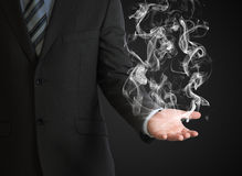 Businessman in a suit holds smoke Royalty Free Stock Image