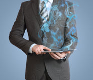 Businessman in a suit holds tablet pc with smoke Stock Photos