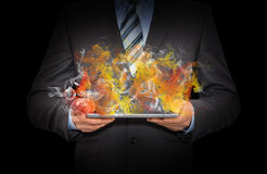 Businessman in a suit holds tablet pc with smoke Royalty Free Stock Photos