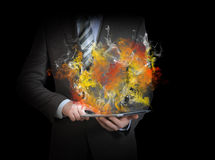 Businessman in a suit holds tablet pc with smoke Royalty Free Stock Images