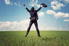 Businessman in suit jumping in field Royalty Free Stock Images