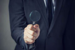 Businessman in suit looking for something using a small magnifier Stock Photo