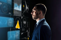 Businessman in suit looking at virtual projection. Business, people and technology concept - businessman in suit looking at virtual projection over black Stock Image