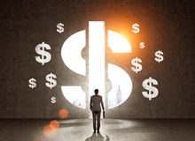 Businessman in suit looking at wall with dollar signs Royalty Free Stock Images