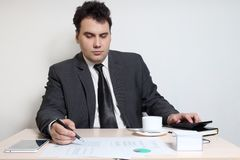 Businessman in suit looks at documents at table with coffee,. Diagrams, documents, tablet PC royalty free stock image