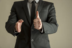 Businessman in suit making a thumbs up gesture Royalty Free Stock Image