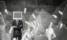 Businessman with monitor instead of head. Businessman in suit with monitor instead of head keeping arms crossed while standing against flying papers and Stock Photography