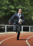 Businessman in suit and necktie carrying folder running desperate in stress on athletic track Stock Images