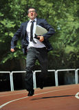 Businessman in suit and necktie carrying folder running desperate in stress on athletic track Stock Photography