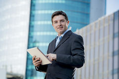 Businessman in suit and necktie holding digital tablet standing outdoors working outdoors business district Royalty Free Stock Image