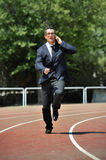 Businessman in suit and necktie running in stress on athletic track talking on mobile phone overworked Royalty Free Stock Photo