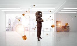 Businessman with an old TV instead of head. Businessman in suit with an old TV instead of head keeping arms crossed while standing among flying and glowing Royalty Free Stock Photos