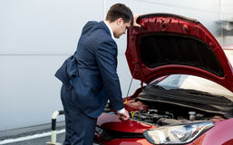 Businessman in suit opening bonnet of open car. Young businessman in suit opening bonnet of open car Stock Images