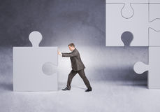 Businessman in suit pushing grey puzzle piece Royalty Free Stock Photo