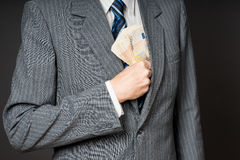 Businessman in suit putting banknotes in his jacket breast pocket.  Business man is holding cash, stack of fifty euros money. Pers Royalty Free Stock Photography